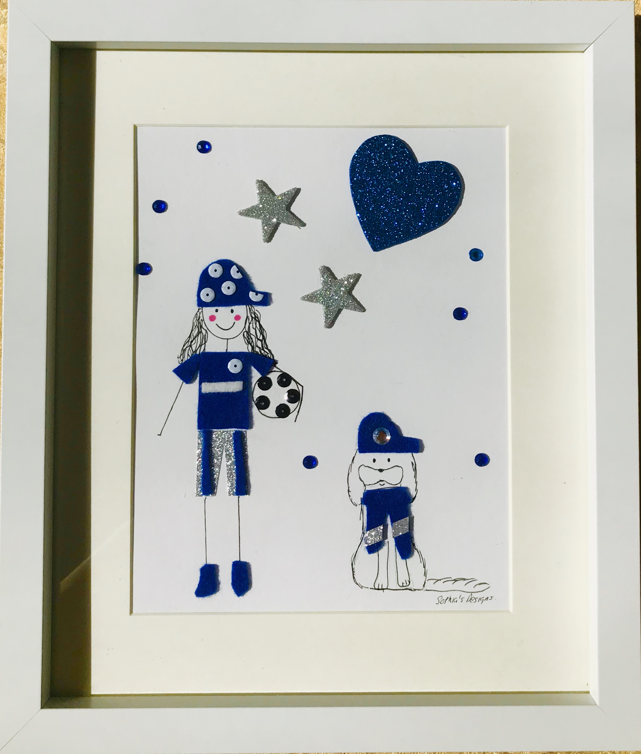 Girl footballer in blue and silver with dog framed wall art